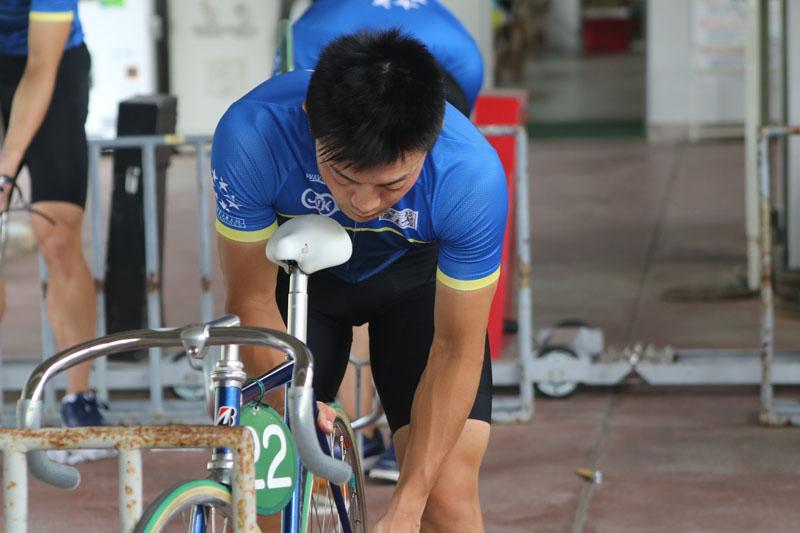 訓練の合間に自転車の整備を行う窪木